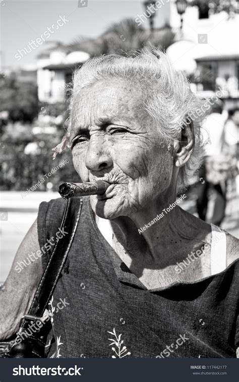 Old Wrinkled Woman Red Flower Smoking Stock Photo